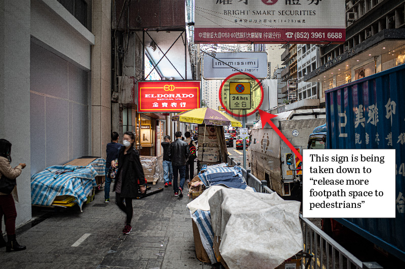 Crowded street scene in central Hong Kong, showing a road sign which will be removed
