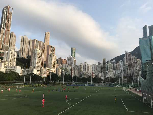 Artists view of the renovated Happy Valley Recreation Ground in Hong Kong, showing soccer pitches and footballers surrounded by the tall apartment buildings of Happy Valley
