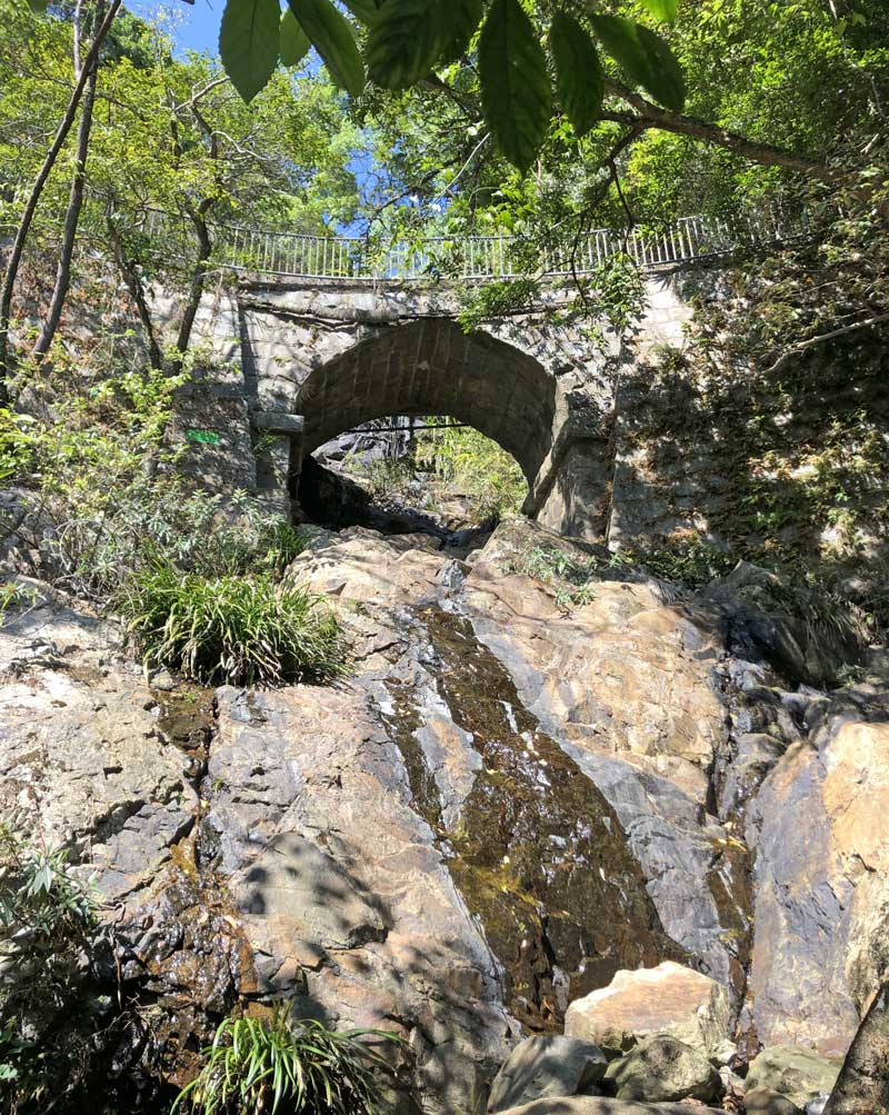 Looking up at Lugard Road waterfall bridge from a stream tributary, bright blue sky and green foliage against the rocky dried up stream bed