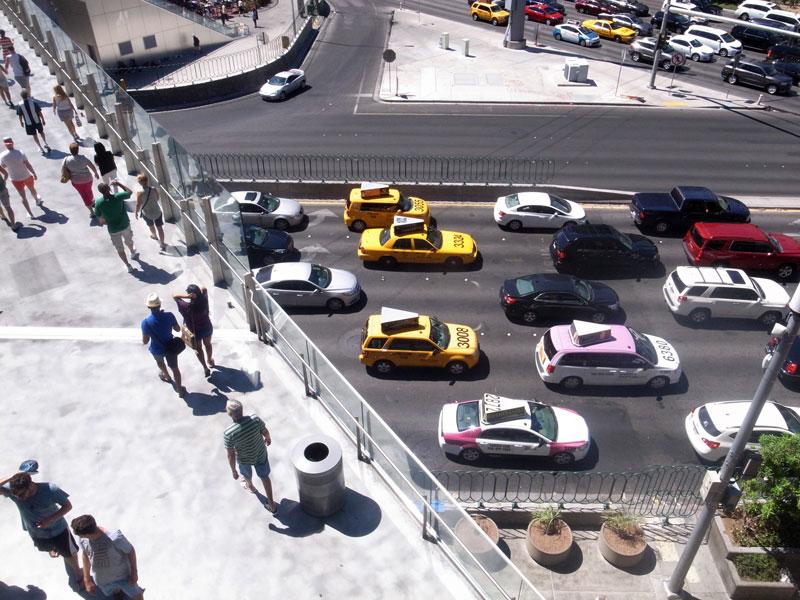 Pedestrians walk on a bridge above many lanes of car traffic in Las Vegas, Nevada