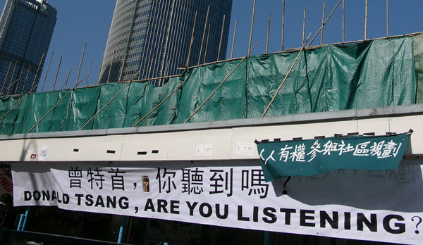 Protest sign which reads Donald Tsang Are You Listening, at the site of the former Star Ferry pier in Central, with IFC skyscaper behind it