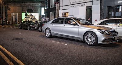 A silver Mercedes S-class double parks against a row of illegally-parked limos on Hong Kong's Queens Road Central, at nighttime, with double yellow lines visible in the foreground