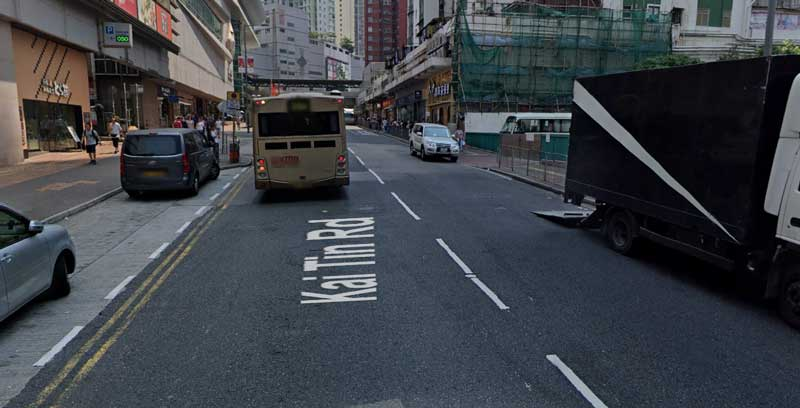 Kai Tin Road, a bus and illegally parked vehicles all around, reducing visibility, a common road scene in Hong Kong