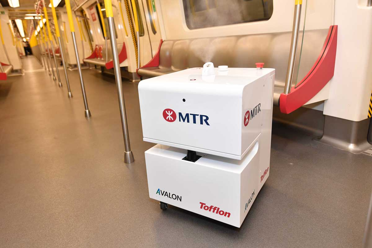 A small white robot sits in an MTR train carriage. It is cuboid in shape with a slit like a photocopier output tray in the middle. It cleans the carriages by spraying bleach.
