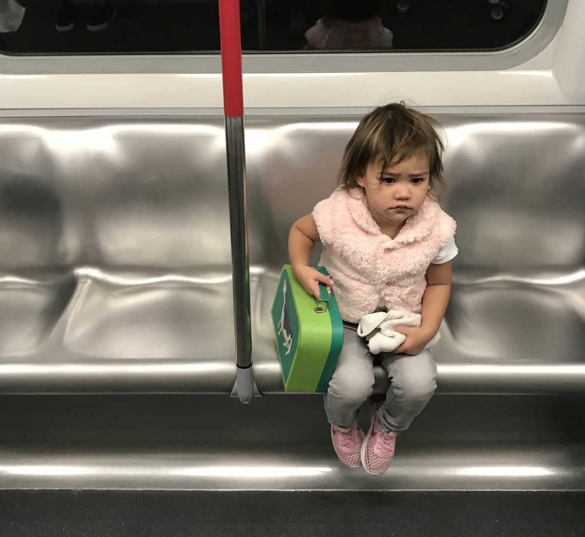 A toddler sits on an MTR train, looking forlorn and clutching her little green suitcase