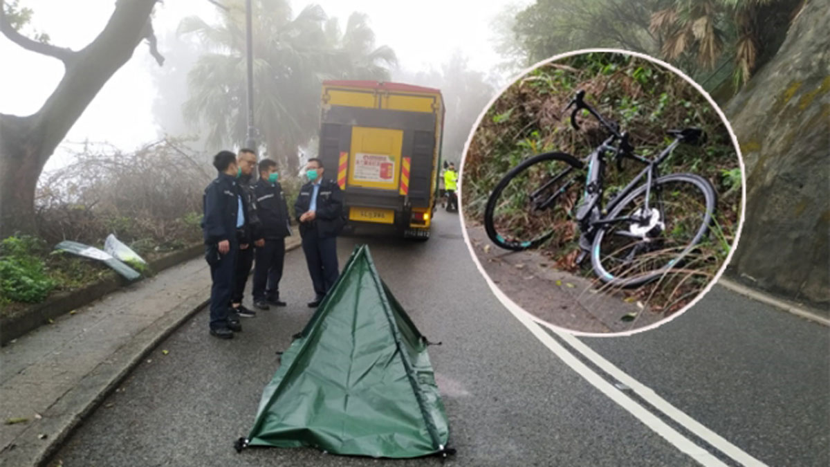 Police stand over the covered body of a cyclist killed on Peak Road this morning after a collision with a goods vehicle in Hong Kong