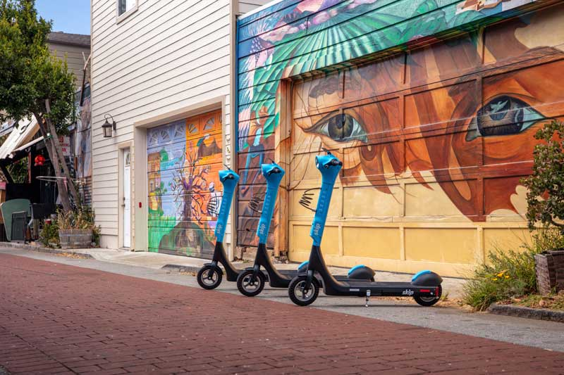 """Three bright blue Skip scooters in front of a colourful """"eyes motif"""" garage door in San Francisco"""