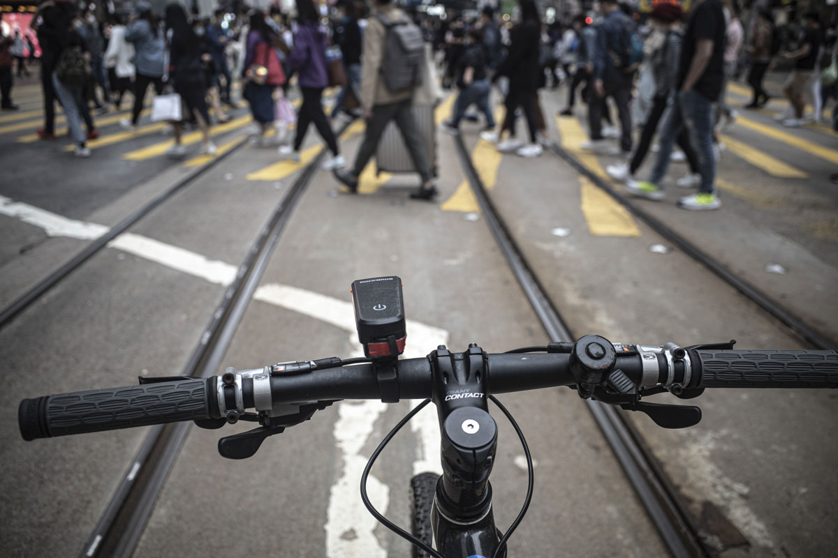 View from a bike, the handlebars in focus in the foreground showing a Giant short stem and a crowd of people crossing a road in the background