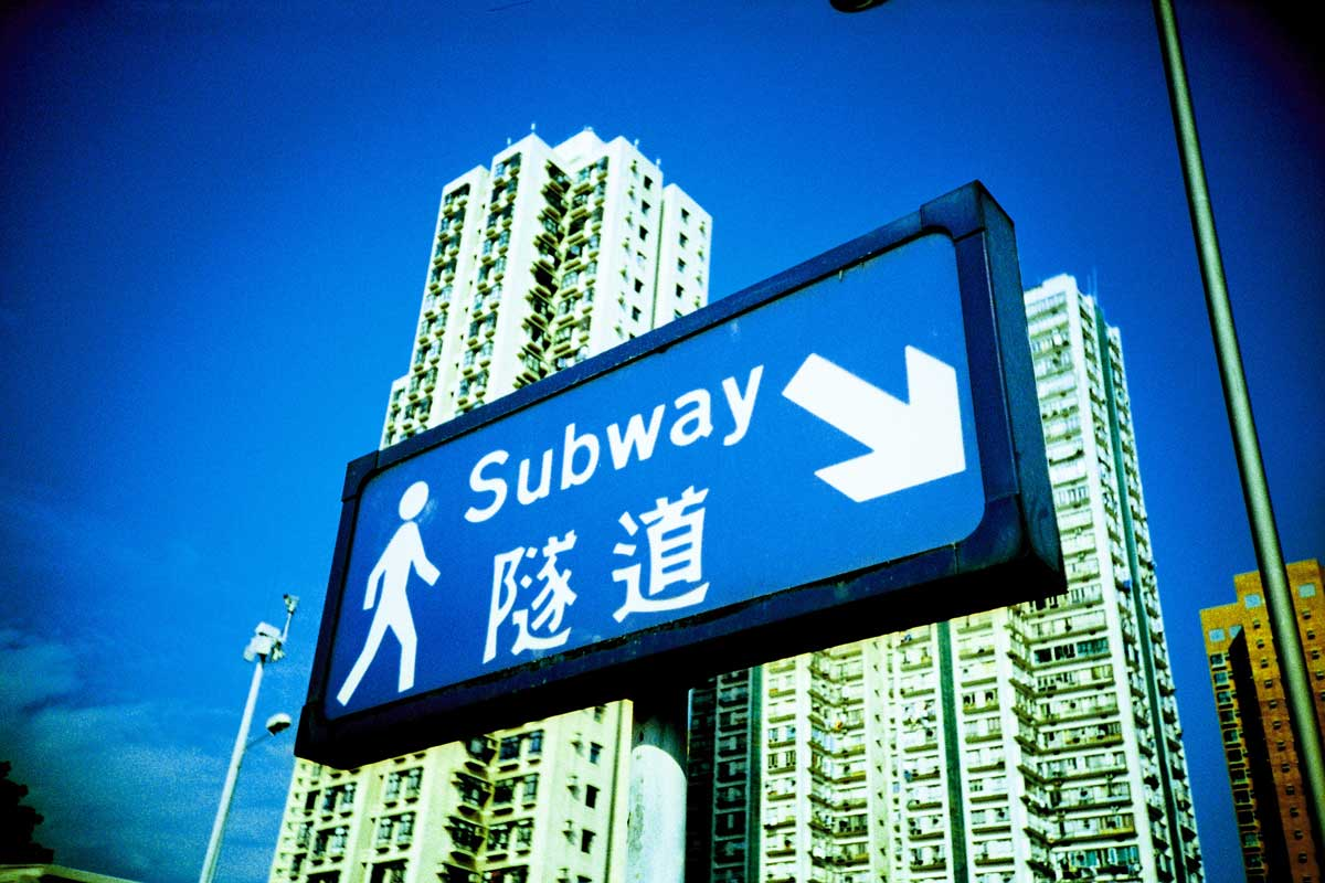 a blue subway sign against a bright blue hong kong sky, public housing in the background