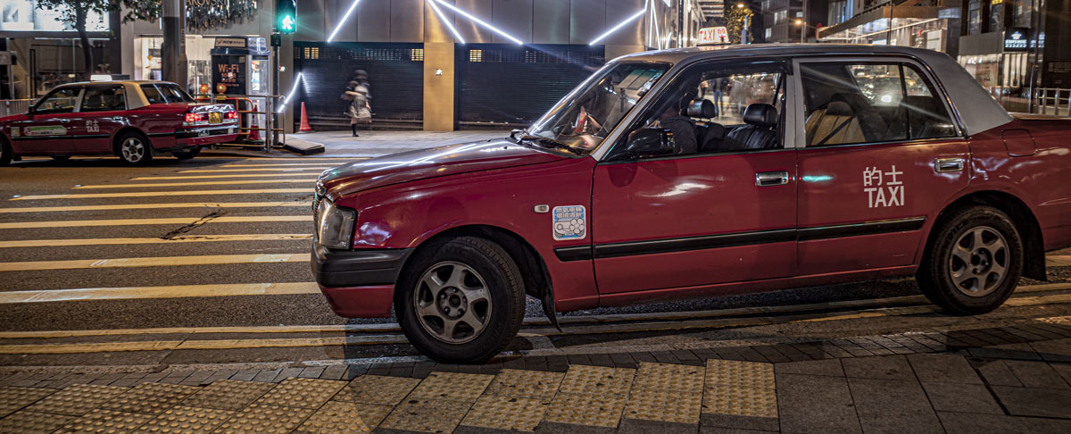 A taxi parks illegally on double yellow lines and a pedestrian crossing, a nighttime scene with the red Hong Kong taxi against Hong Kong's neon