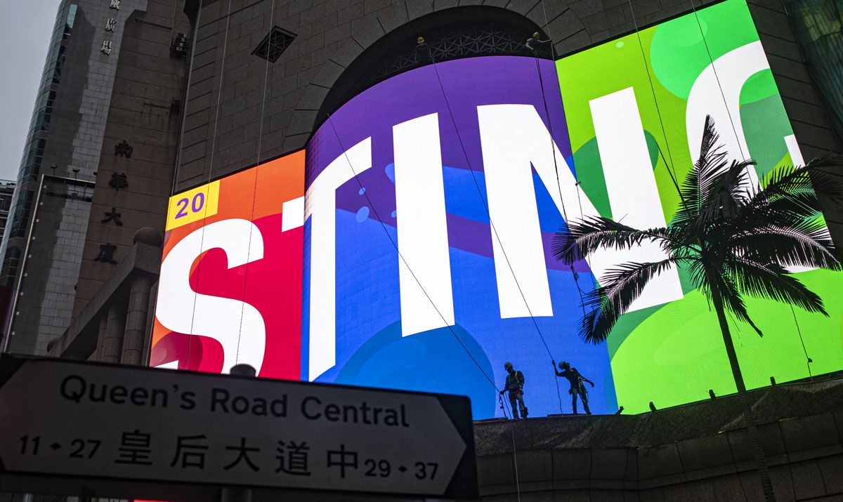 A gigantic billboard under test in Central Hong Kong Enternatinment building, showing red green and blue and the word STING, so bright the daylight is reduced to a dim background