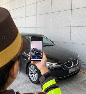 Female traffic warden in brown hat takes a photo of a black BMW at a police station in Hong Kong, demonstrating the new traffic tool e-ticketing system