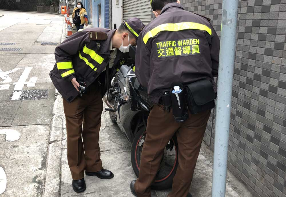 Two Hong Kong traffic wardens in their brown uniforms ponder a black motorbike parked illegally on the pavement