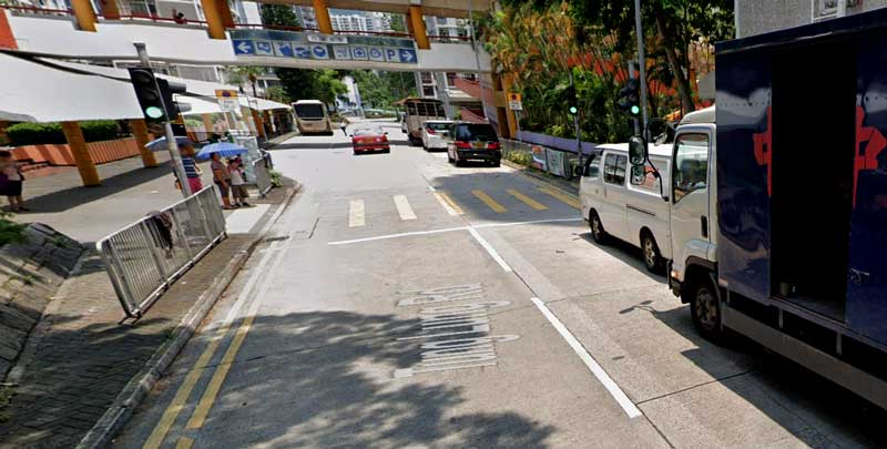 Street scene of a one way street in Wong Tai Sin, showing cars illegally parked and turning a two-lane road into a single carriageway