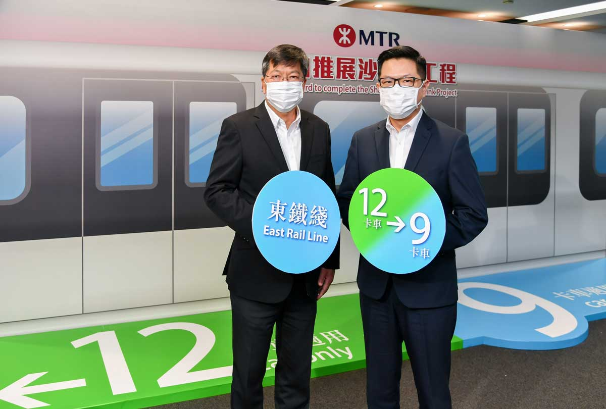 Two masked officials from Hong Kong's MTR show signs showing the reduction in train length from 12 carriages to 9 carriages