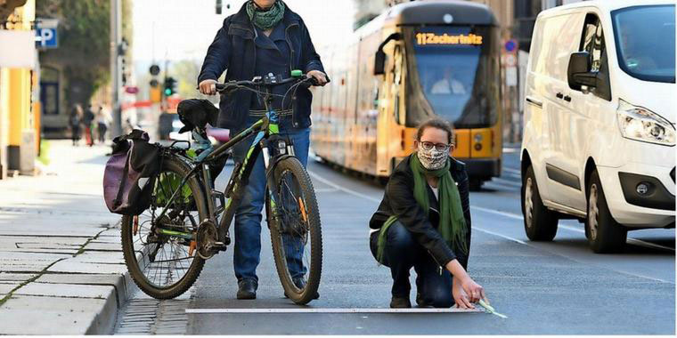 An activist measures out a temporary cycle lane in Dresden, Germany