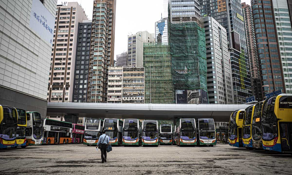 A bus park against a bank of skyscrapers in Hong Kong's Sheung Wan, with a man walking to his bus