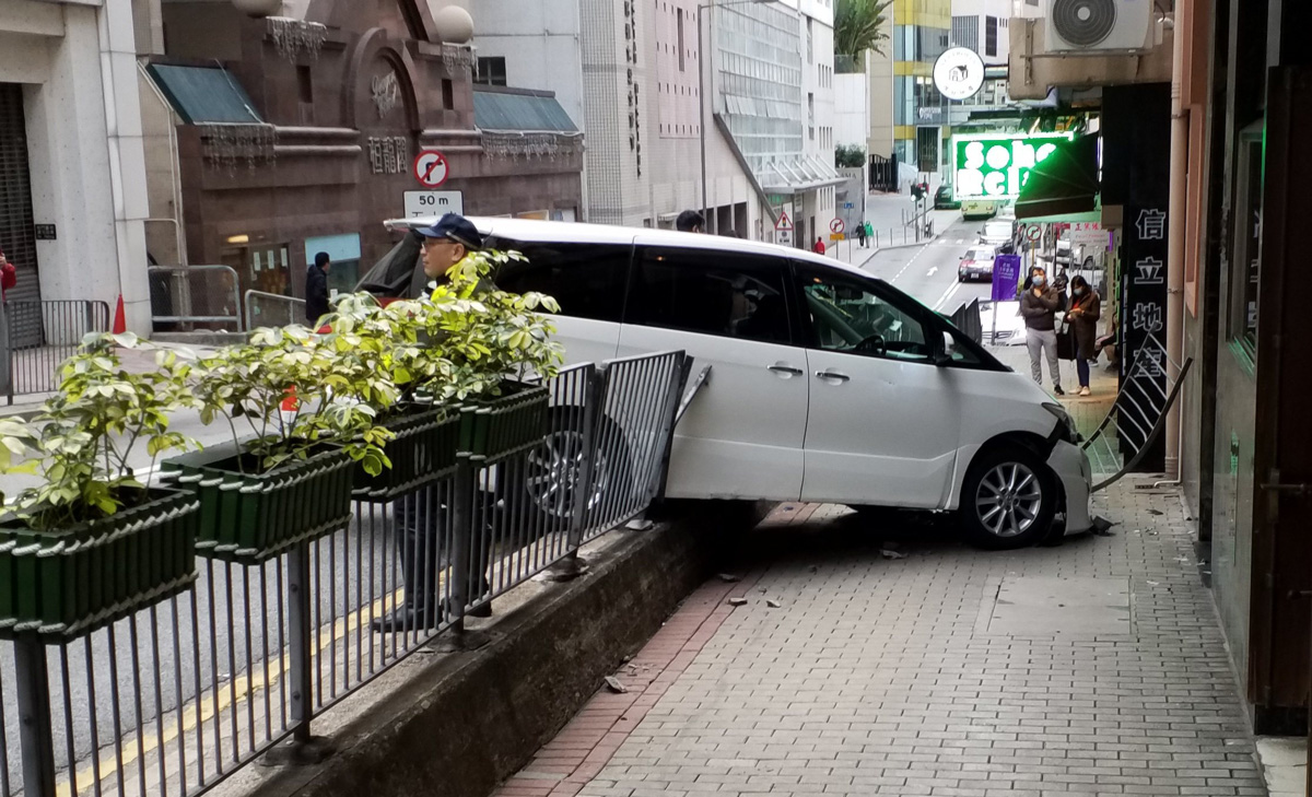 A white van which smashed through railings after breaking a woman's hand on Caine Road in Hong Kong