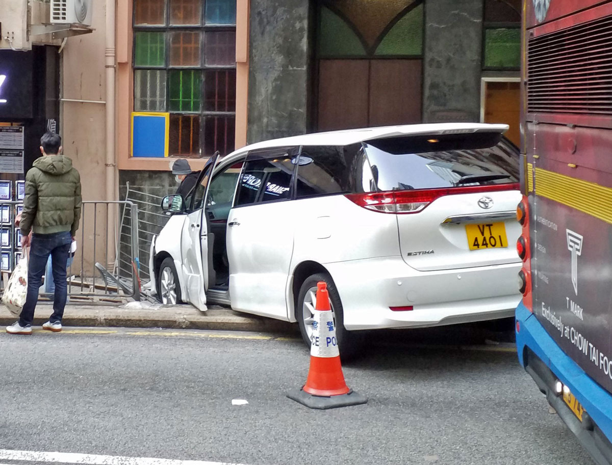 A white van stuck in railings after striking a young woman and breaking her hand
