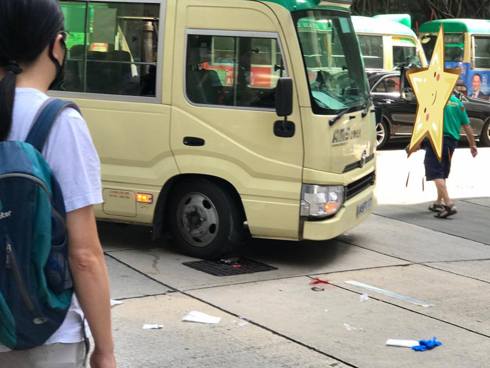 Blood and surgical gloves remain in the street after a woman was rushed to hospital following a minibus crash at a Kennedy Town blackspot