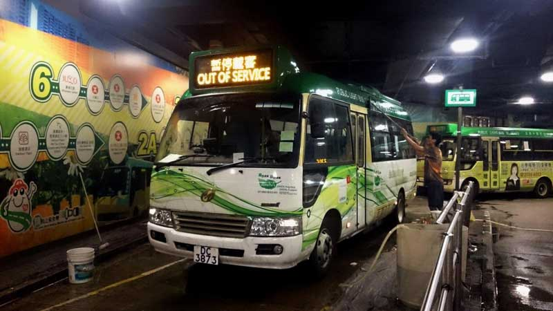 A green minibus being cleaned at a terminal in Hong Kong, the display board reads Out of Service