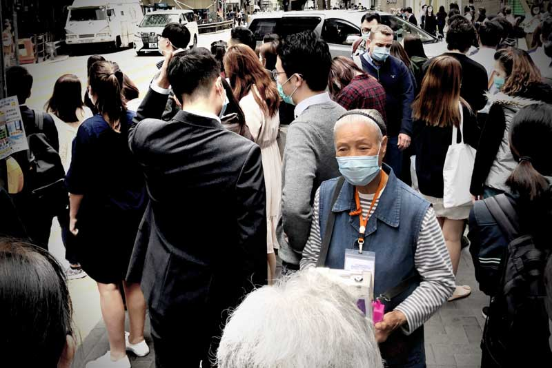 An elderly pedestrian is jostled by crowds waiting to cross a road on a busy Hong Kong pavement, Central Hong Kong