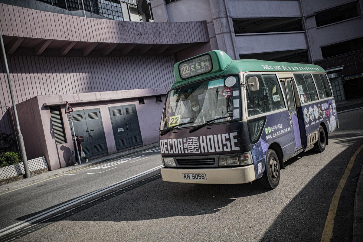 A green minibus corners a road in Hong Kong