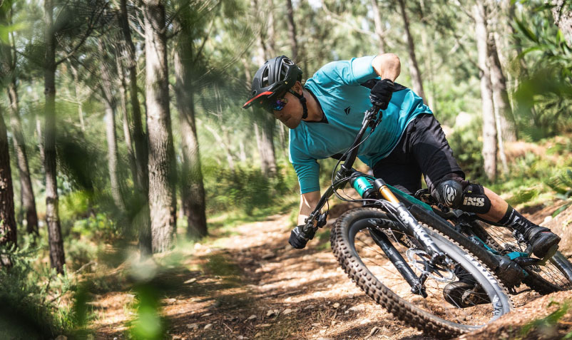 A mountain biker storms down a wooded trail