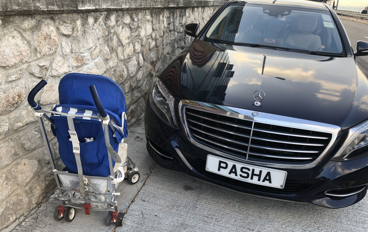 A large black Mercedes Benz S-class completely blocks the pavement, with a baby stroller struggling to get past, on a Central street in Hong Kong, license plate PASHA