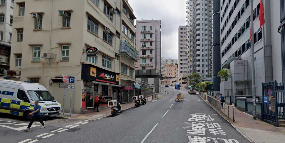 Scene of a road in Happy Velley, Hong Kong, showing a police station with dual Hong Kong and China flags hanging limply down from flagstaffs