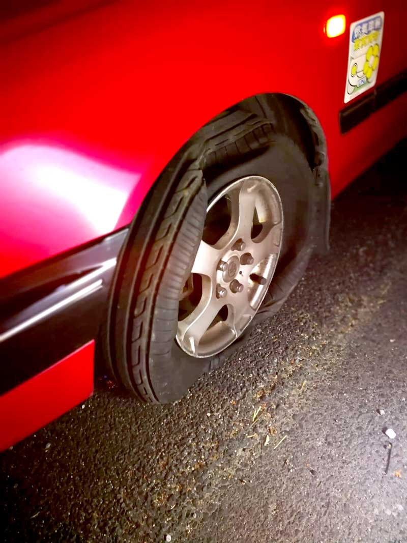 A taxi tyre ripped apart, still on the wheel, after rocks were thrown on the highway at Tolo Highway Hong Kong