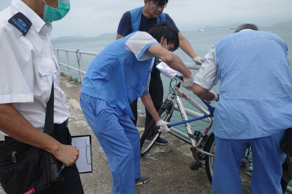 A worker uses bolt cutters to cut the lock on an illegally parked bike on Lamma Island