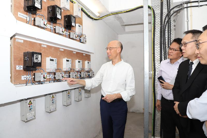 Secretary for Environment inspects a rack of switchgear in a car park while a team look on