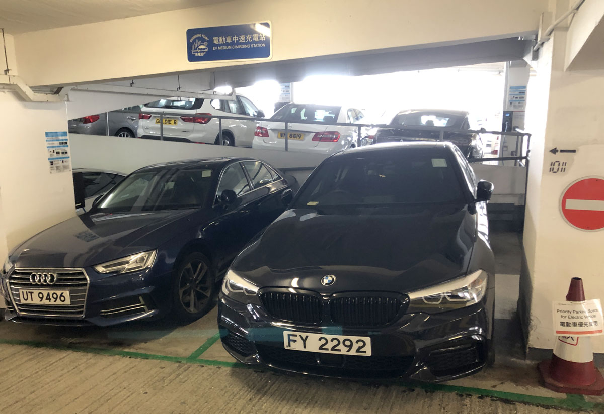 """Two petrol cars sit in the """"electric vehicle"""" charging point in  Central Hong Kong car park"""