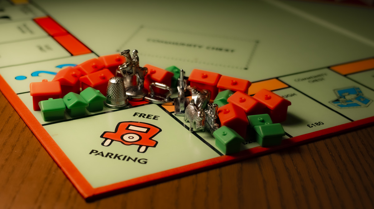 a Monopoly board with pieces crowded around the free parking space