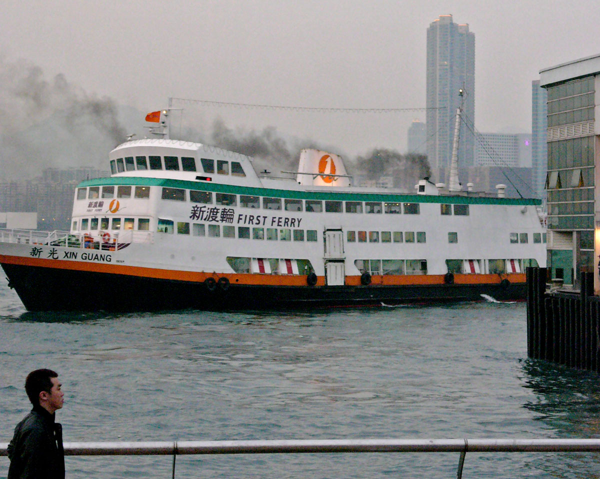 A ferry berths in Hong Kong, emitting clouds of black smoke