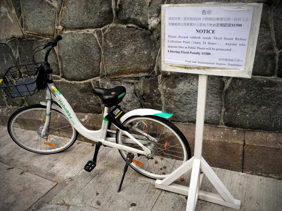 A white dockless bike standing on a street next to an old Hong Kong wall, with a sign planted next to it warning of penalties for littering