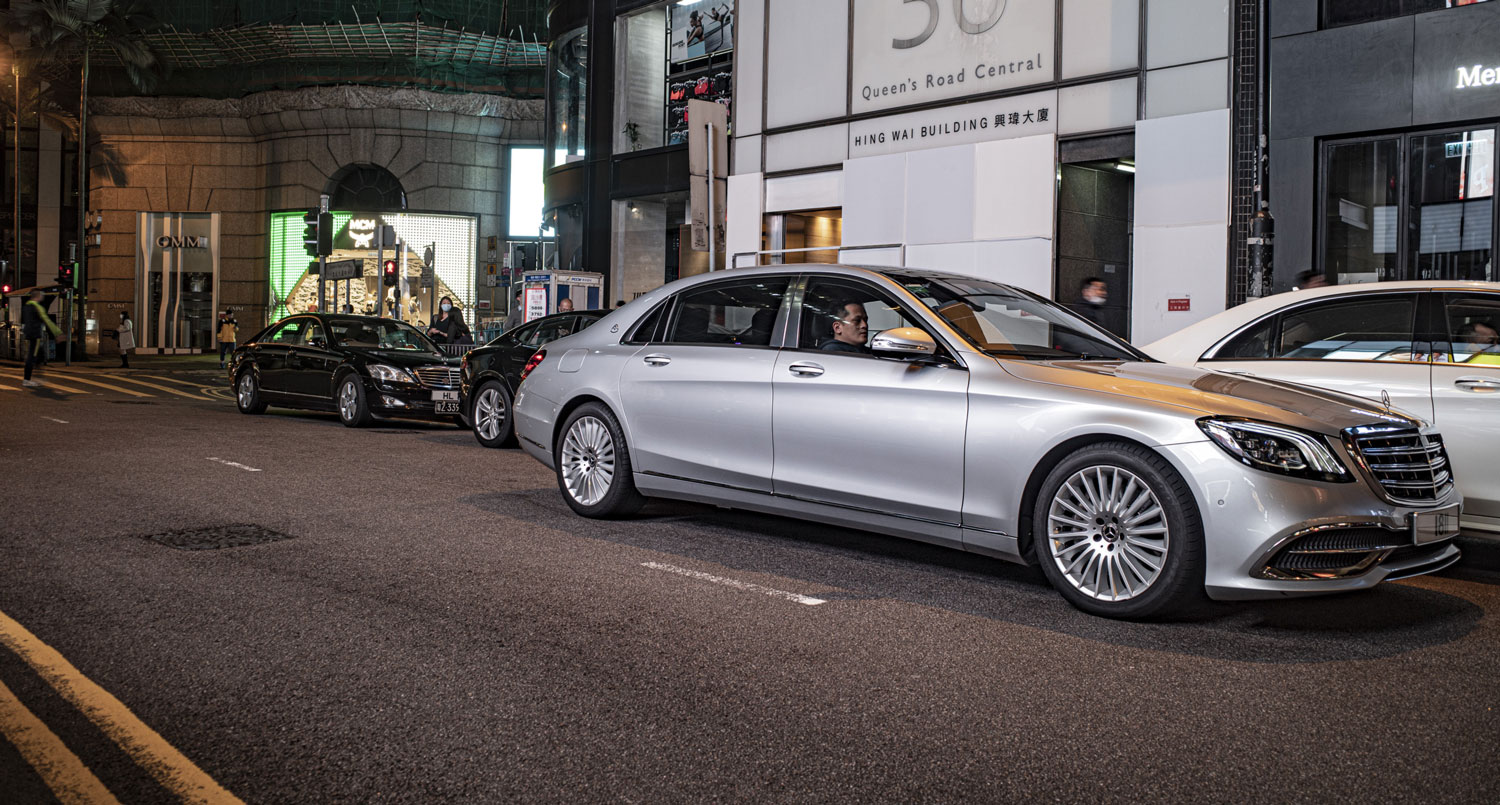 A luxurious silver S-class Mercedes bloxks Queen's Road Central by double parking, while many other limos park illegally in the background