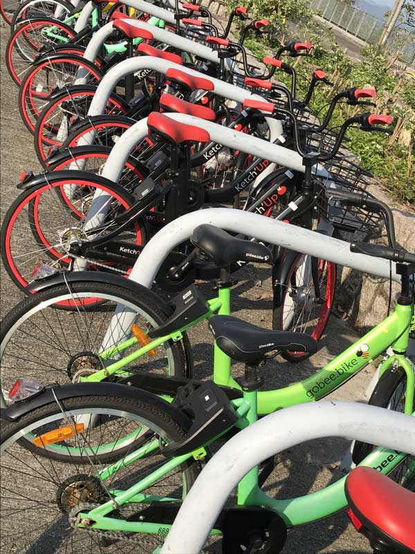 A row of brightly coloured dockless bikes in Hong Kong, some green, some black and red