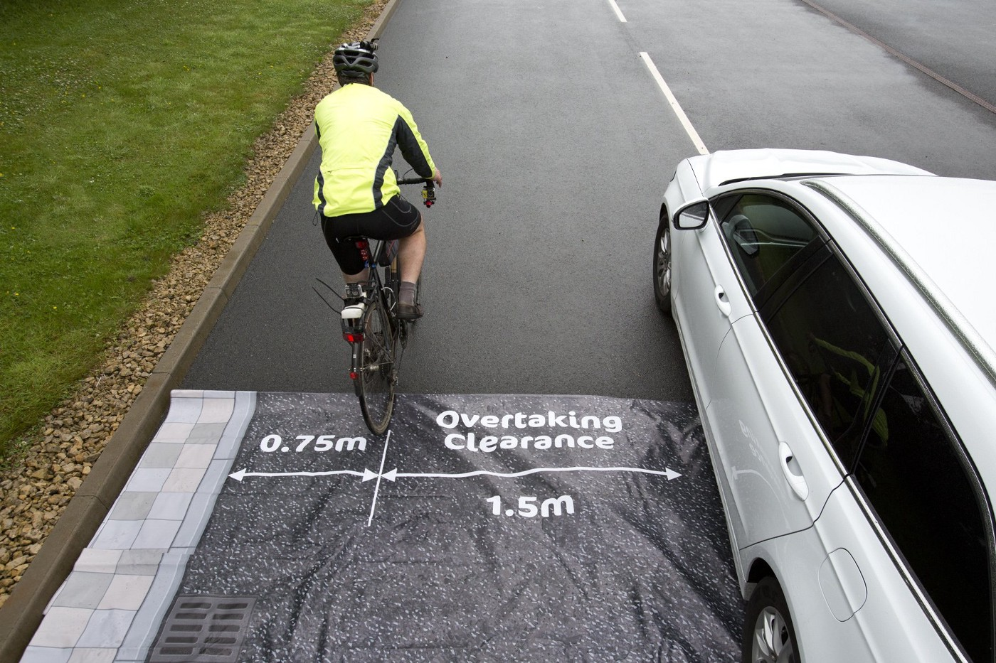 A cyclists being overtaken on a road with markings to show the safe distances for such a manouvre