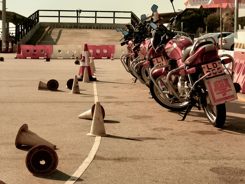 A row of learner motorbikes at a driving test centre, with knocked over cones and in the distance the infamous ramp where figure-of-eight on a slope presents a driving test challenge