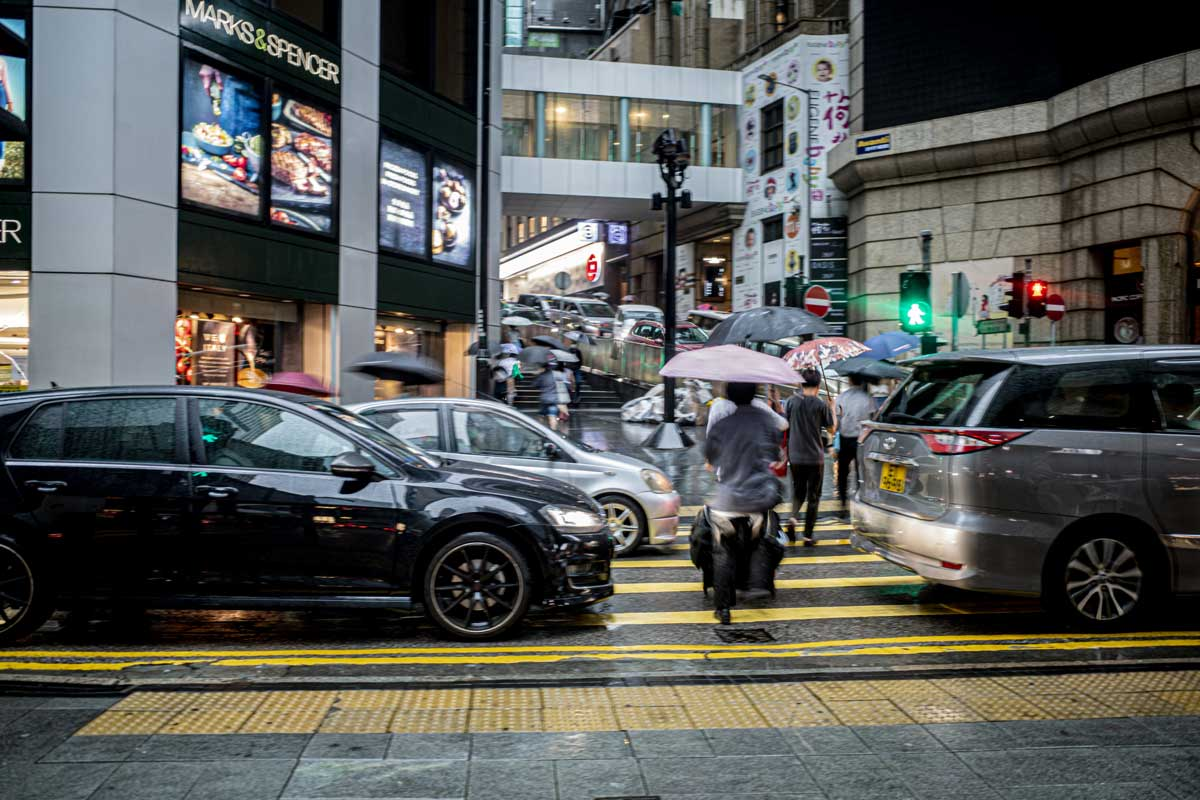 Cars block a pedestrian crossing in Hong Kong, with pedestrians squeezing through in the rain with umbrellas