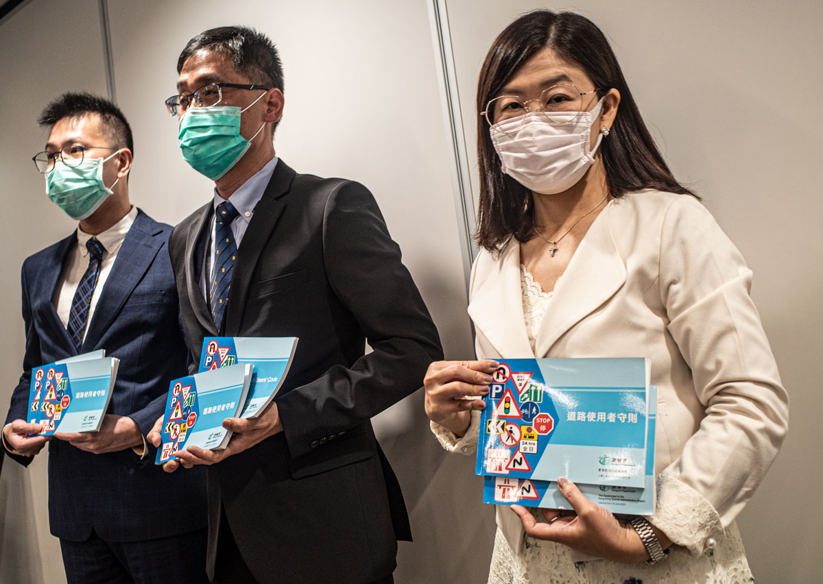Chris Ho, left, Eddy Wu centre and Louisa Fung right show the new Road Users' Guide in Hong Kong