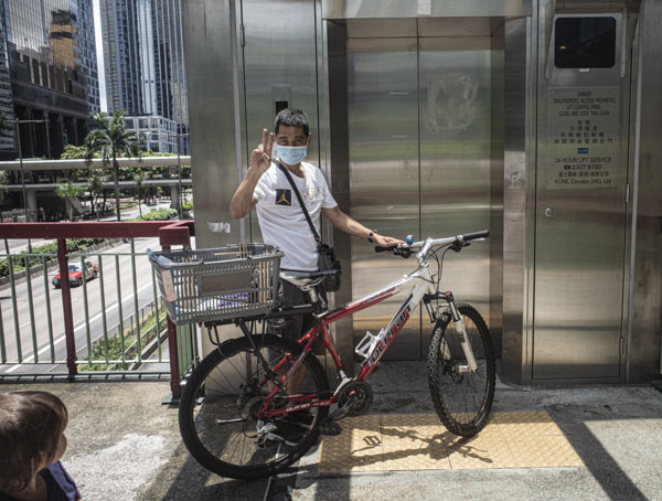 A delivery cyclist waiting for a life on a footbridge in Wan Chai