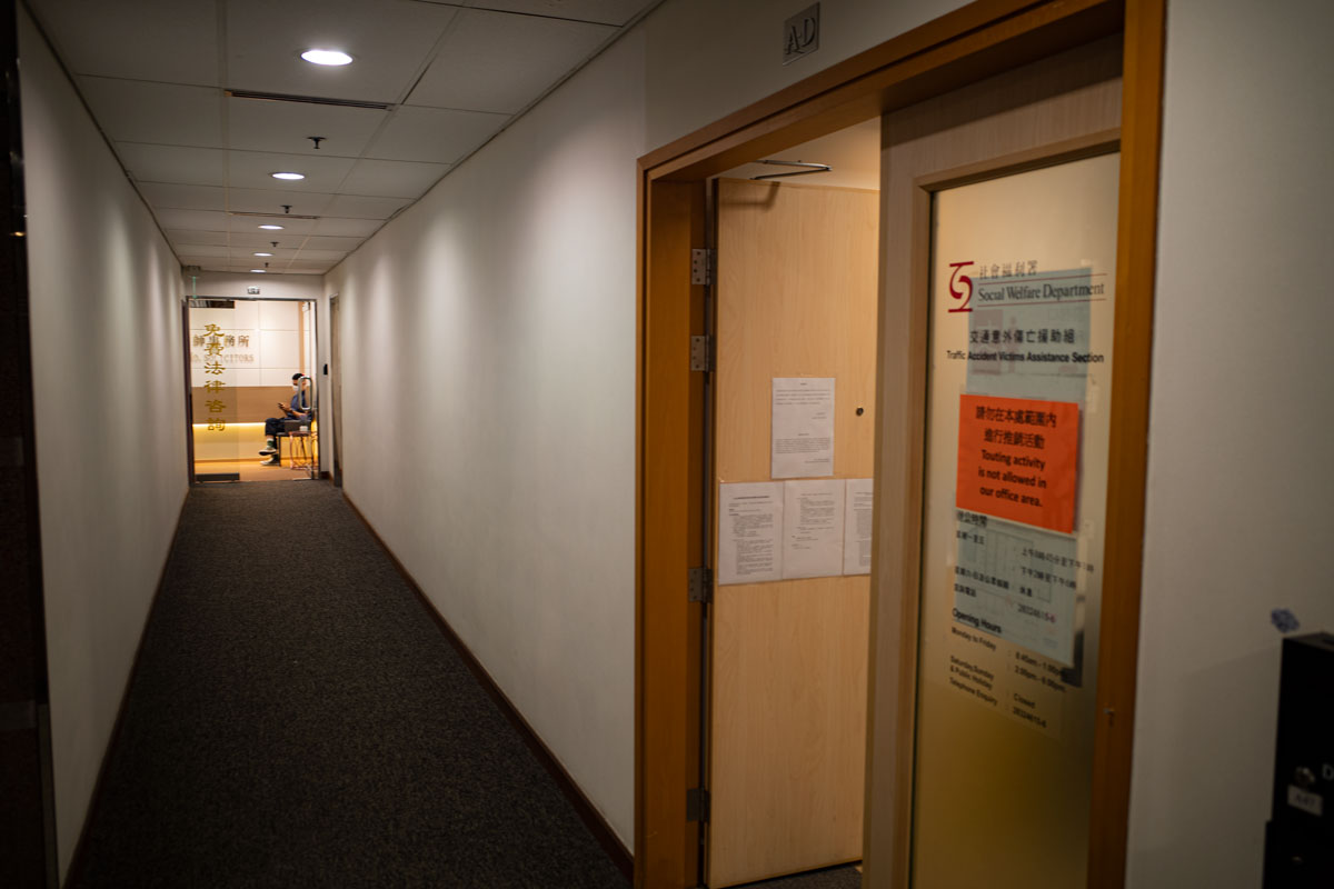 A law clerk sits on a chair at the end of a corridor, keeping an eye on the comings and goings of a social welfare officer