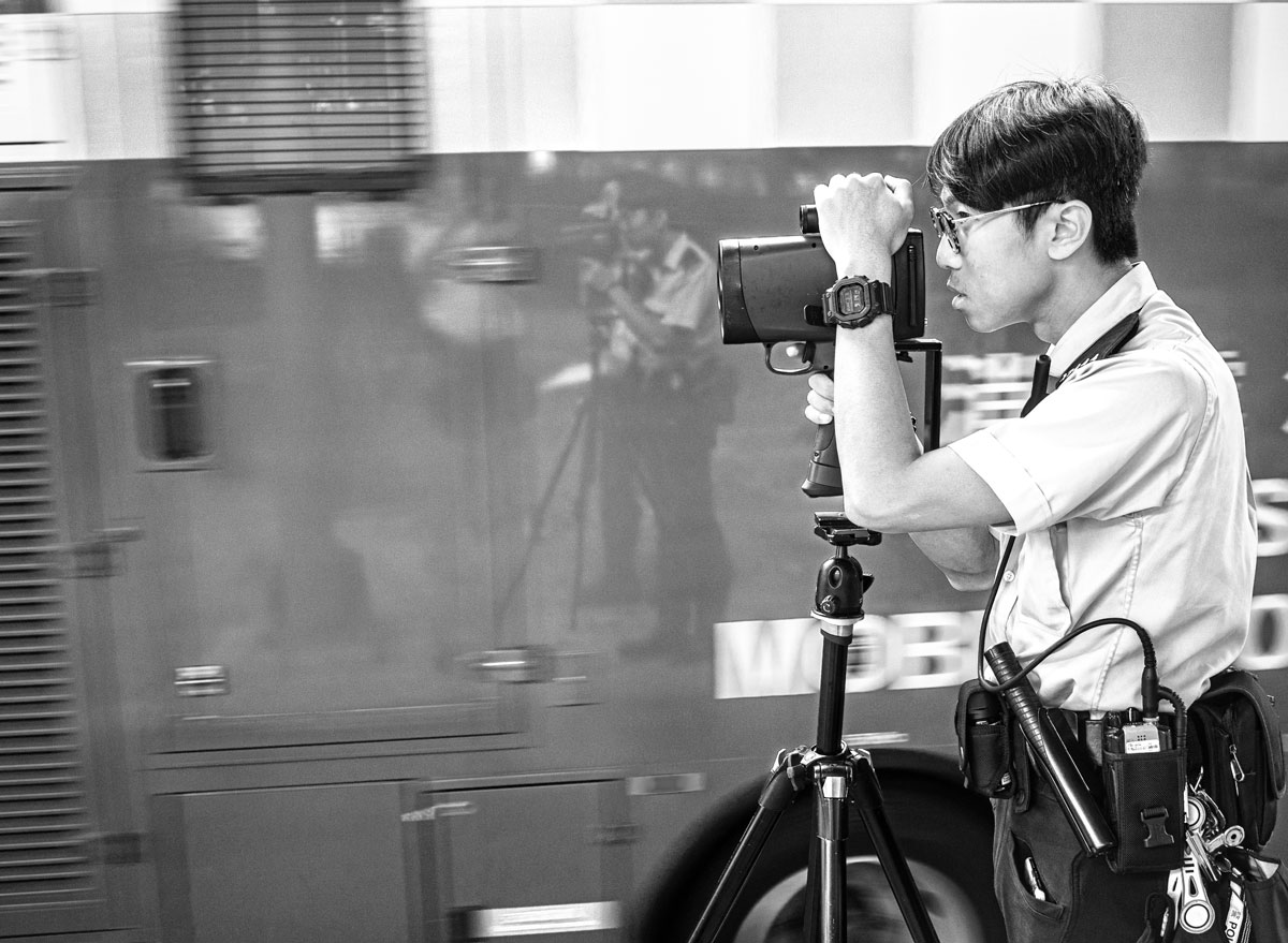 A police officer uses a mobile speed camera on a tripod in Hong Kong