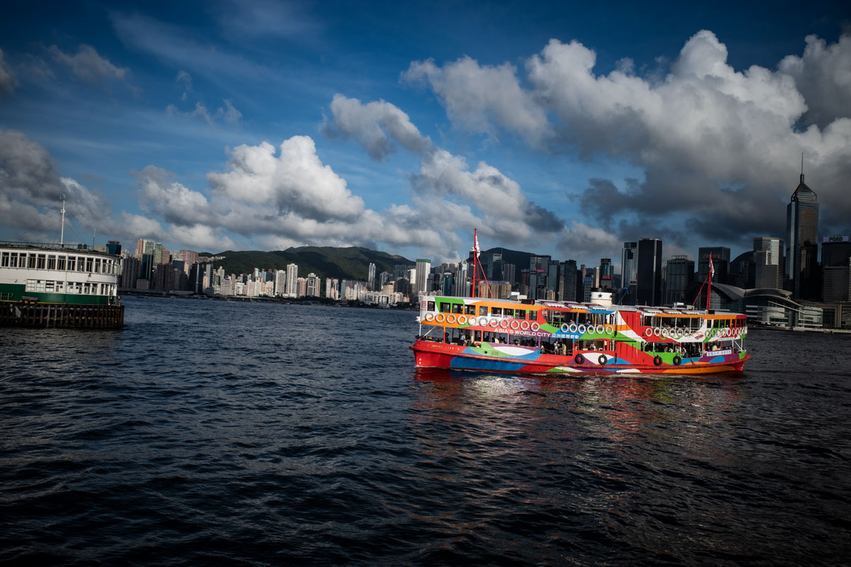 A brightly coloured red ferry crosses the dramatic skyline of Hong Kong's Victoria Harbour