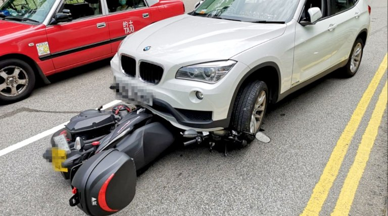A scooter jammed underneat a white BMW following a fatal crash earlier today in Hong Kong